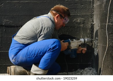 Construction worker making a culvert in foundation wall for sewage pipe using pneumatic hammer