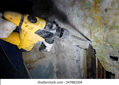Construction worker making hole a using pneumatic hammer
