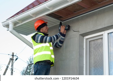 construction worker mounts a soffit on the roof eaves