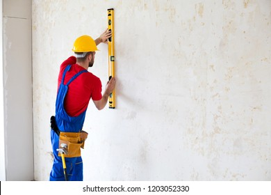 Construction worker observing and surveying wall alignment using water level