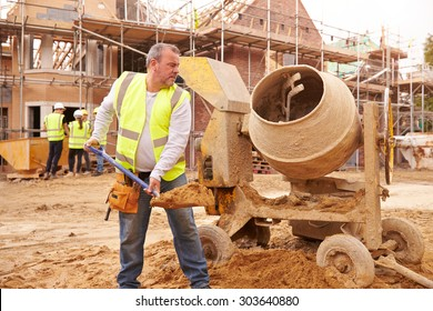 Construction Worker On Building Site Mixing Cement