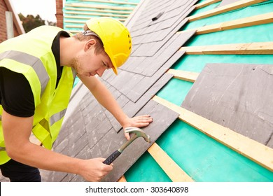 Construction Worker On Building Site Laying Slate Tiles