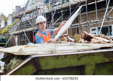 Construction Worker On Building Site Putting Waste Into Rubbish Skip