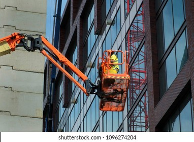 construction worker on an orange elevated platform on a large modern building site
