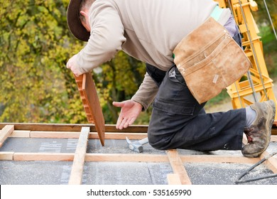 construction worker on a renovation roof covering it with tiles using hammer, crane and grinder