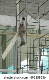 construction worker on scaffolding without harness - unsafe work practice without personal protective gear