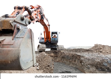 A construction worker operating a track hoe machine that is sitting on dirt with an isolated sky background.