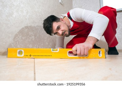 Construction worker in overalls sitting checks the quality level of flat floor tiles in the house