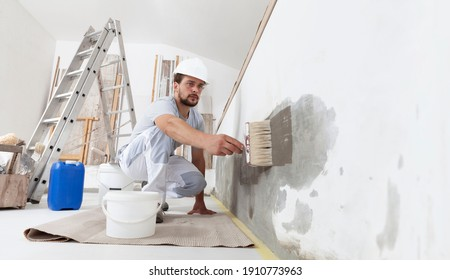 construction worker painter man with protective helmet, brush in hand and buckets of products to restore and paint the wall, indoor the building site of a house