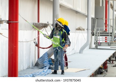 Construction worker painting color wall at construction site