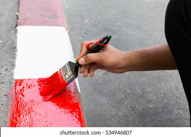 construction worker painting curb