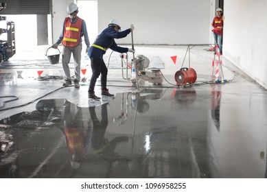Construction worker painting epoxy flooring or floor hardener