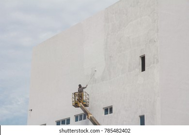 A construction worker painting a newly built building. A crane truck is used to raised him up.