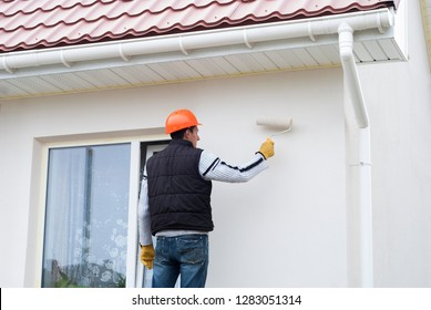construction worker is painting a wall with a roller