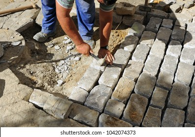 Construction worker paving a city street with granite cobblestones