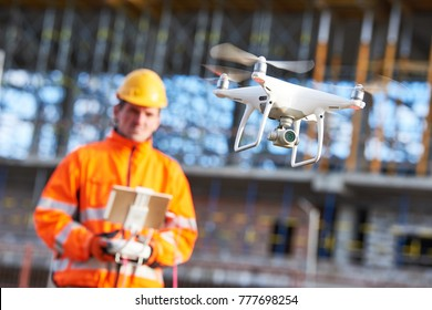Construction worker piloting drone at building site. video surveillance or industrial inspection