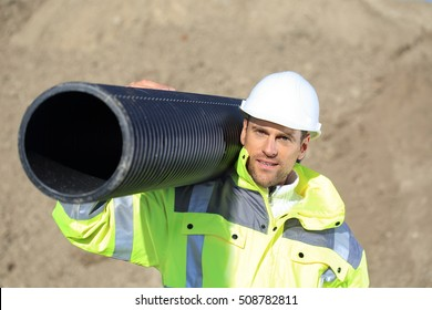 A Construction worker with a pipe on his shoulder