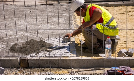 a construction worker places paving blocks on a street street. well-equipped with a helmet working under the hot sun in Bourgas/Bulgaria/04.26.2018. Editorial use only. person on road infrastructure.