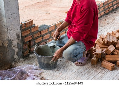 Construction worker placing bricks on cement for building exterior walls.