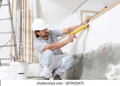 construction worker plasterer man uses caulking gun in building site of home renovation with tools and building materials on the floor