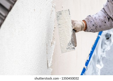 Construction worker plastering and smoothing concrete wall with cement.