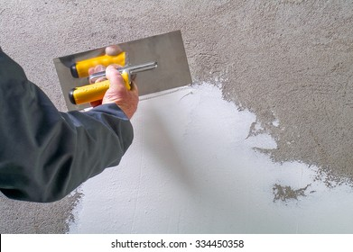 Construction worker - plastering and smoothing concrete wall with white cement by a steel trowel - spatula aligns