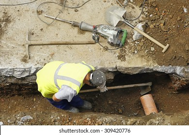 construction worker with pneumatic hammer drill , pick and shovel to repair  water and sewer pipes
