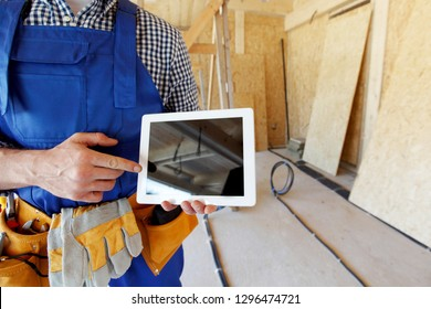 Construction worker pointing at digital tablet at construction site