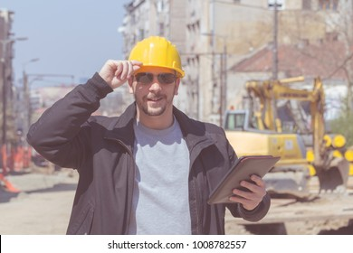 Construction worker posing with his tablet outdoors.