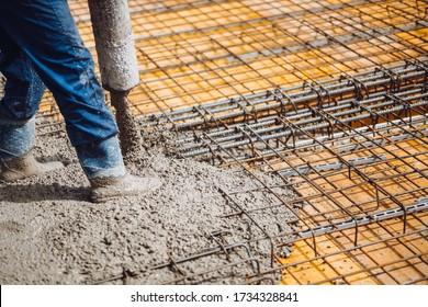 Bauarbeiter gießt Zement oder Beton mit Pumpenschlauch. Stabstahl und Stangen