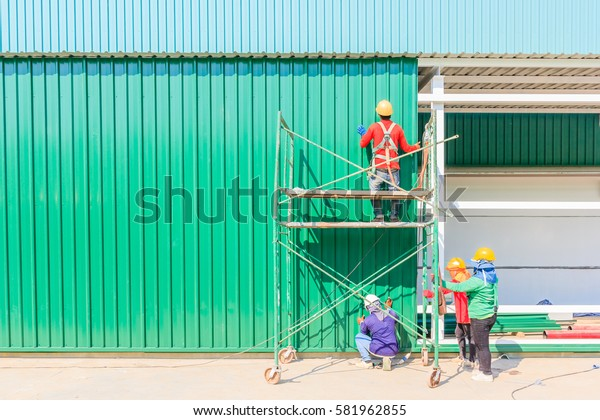 Construction worker in protective uniform and protective helmet install a steel sheet metal profiles in a construction site