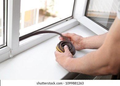 Construction worker putting sealing foam tape on window indoors