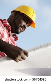 Construction worker reading plans outside