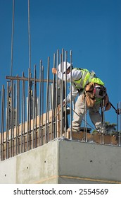 A construction worker releasing a concrete form from a wall.