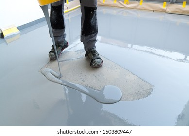 A construction worker renovates balcony floor and pours watertight resin and glue before chipping and sealing