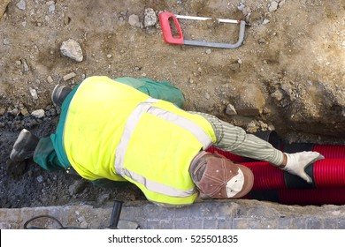 construction worker repair water , optical fiber and electric  pipes in road excavation in street construction site