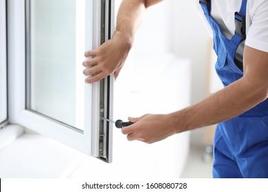 Construction worker repairing plastic window with screwdriver indoors, closeup