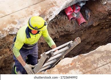 Bauarbeiter für die Wiederherstellung und Reparatur von Rohren für die unterirdische elektrische Leitung , Schwerpunkt im Hintergrund