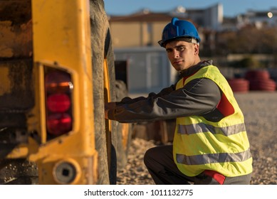 Construction worker revise excavator tire