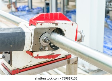Construction Worker sawing a pipe by portable orbital pipe cold cutting machine