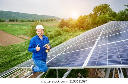 Construction worker with screwdriver looking in camera with thumb-up gesture on photo voltaic panel solar system shiny surface and lit by sun green fields background. Alternative energy concept.