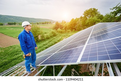 Construction worker with screwdriver standing on metal frame of photo voltaic solar system looking on shiny surface. Alternative energy, ecology protection and cheap electricity production concept.
