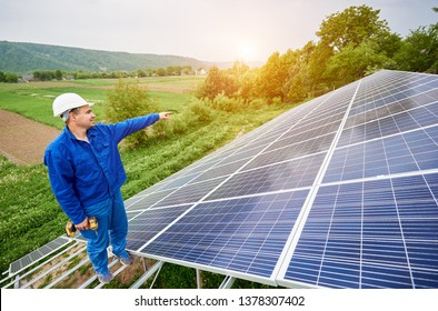 Construction worker with screwdriver standing on metal frame of photo voltaic solar system pointing on shiny surface. Alternative energy, ecology protection and cheap electricity production concept.
