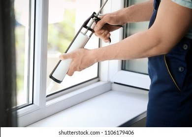 Construction worker sealing window with caulk indoors
