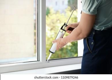Construction worker sealing window with caulk indoors
