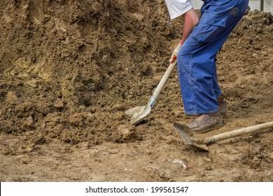 Construction worker shoveling dirt,  shoveling ground. Worker with shovel. Selective focus.