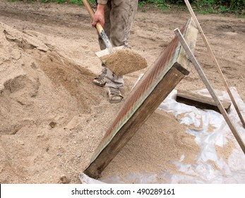 Construction worker sifting gravel through a sieve with shovel.