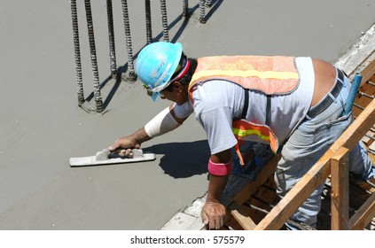 Construction worker smooths concrete