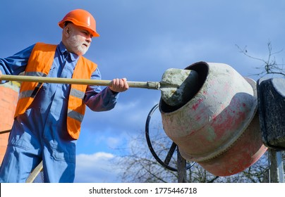 Construction worker with spade in hand. Builder works with concrete mixer. Concrete mixer prepares cement mortar. Handsome construction worker on building industry construction site. Cement creation.