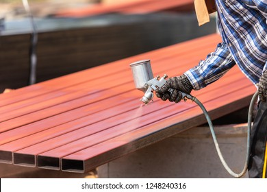 Construction worker spraying paint to steel pipe to prevent the rust on the surface